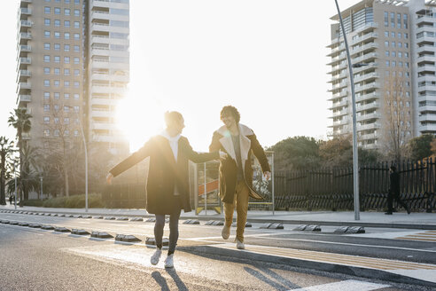 Happy couple running in the city at sunset - JRFF02705