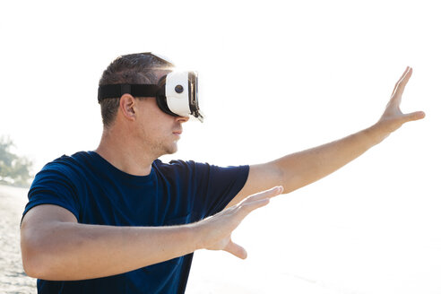 Man wearing VR glasses on the beach - HMEF00224
