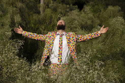 Bearded man wearing suit with colourful polka-dots enjoying nature - KBF00506