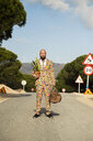 Man wearing suit with colourful polka-dots standing on country road with travelling bag and potted plant - KBF00509