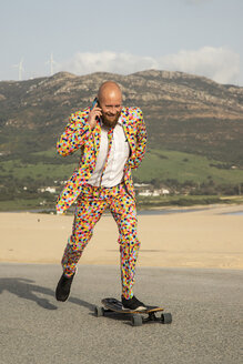 Smiling bald man on the phone wearing colourful suit while skateboarding on road - KBF00515