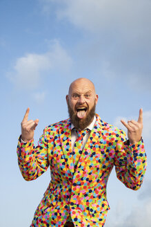 Portrait of bald man with beard  wearing suit with colourful polka-dots sticking out tongue - KBF00524