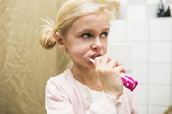 Close-up of girl brushing teeth in bathroom - ASTF04721