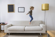 Little girl jumping in the air on the couch at home - PSIF00242