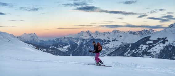 Switzerland, Bagnes, Cabane Marcel Brunet, Mont Rogneux, woman ski touring in the mountains at dusk - ALRF01377