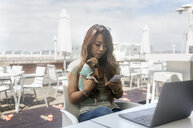 Businesswoman sitting at pavement cafe with her Chihuahua puppy using smartphone - MGOF03947