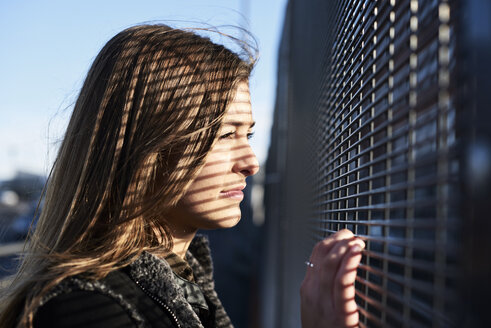 Portrait of young woman with shades on her face looking through metal fence - IGGF00807