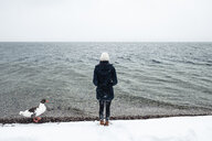 Grey goose and young woman at Lake Starnberg in winter - WFF00008