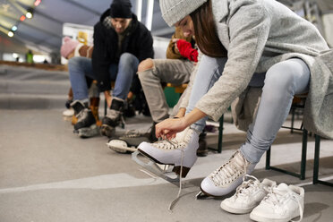 Friends putting on ice skates at an ice rink - ZEDF01873