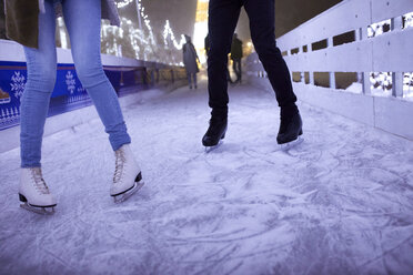 Legs of couple ice skating on an ice rink at night - ZEDF01876