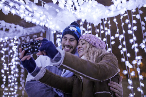 Happy young couple in winter decoration taking a selfie - ZEDF01879