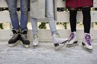 Legs of friends wearing ice skates standing at an ice rink - ZEDF01882