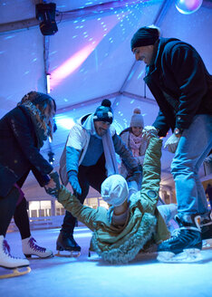 Happy friends ice skating on an ice rink helping man standing up - ZEDF01888