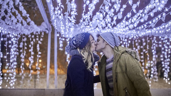 Young couple kissing in winter decoration - ZEDF01903
