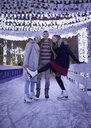 Happy friends on an ice rink at night - ZEDF01912