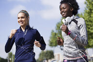 Two happy sporty young women running together in the city - JSRF00117