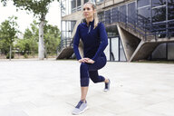 Sporty young woman stretching in city - JSRF00123