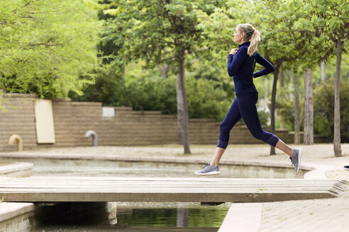 Sporty woman running in a park - JSRF00126