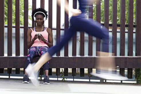 Sporty young women relaxing with runner passing by - JSRF00132