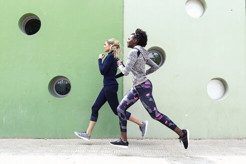 Lleida, Catalonia, Spain,Shot of two sporty young women running together in the city. - JSRF00138