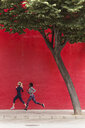 Two sporty young women running together in the city passing red wall - JSRF00141