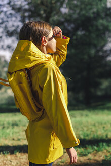 Girl wearing yellow raincoat and yellow backpack standing at sunlight at forest glade - ERRF00771