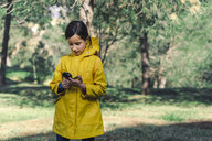 Girl wearing yellow raincoat in nature looking at compass - ERRF00774