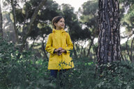 Portrait of girl wearing yellow raincoat  in nature - ERRF00777
