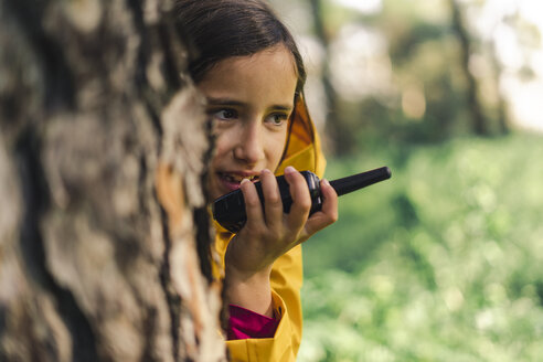 Portrait of girl with walkie-talkie hiding behind tree trunk - ERRF00780