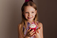 Portrait of happy little girl with cup cake - NMS00289