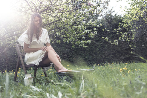 Young woman wearing white dress sittiing in garden taking footbath - WFF00012