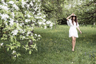 Young woman wearing white dress and floppy hat walking barefoot in garden with blossoming apple trees - WFF00018