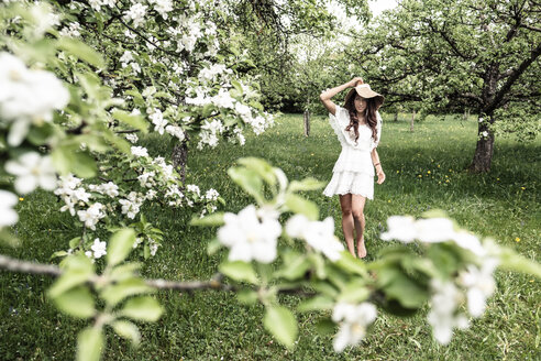 Young woman wearing white dress and floppy hat walking barefoot in garden with blossoming apple trees - WFF00021