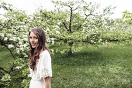 Portrait of smiling young woman in garden with blossoming apple trees - WFF00024