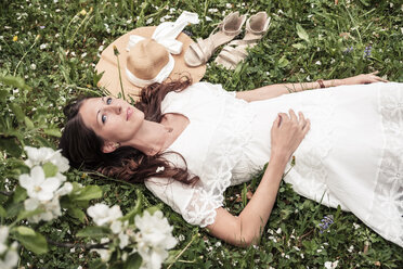 Portrait of daydreaming young woman wearing white lace dress lying on flower meadow - WFF00027