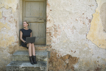 Italy, Tuscany, Monteriggioni, woman sitting at house entrance using laptop - PSTF00297