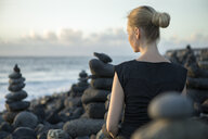 Spain, Tenerife, Costa Adeje, woman sitting between cairns at the coast - PSTF00303