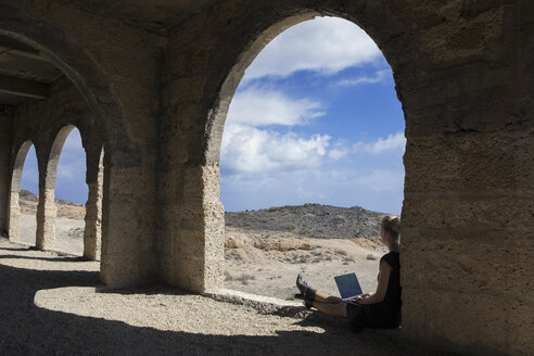 Spain, Tenerife, Abades, Sanatorio de Abona, woman sitting in ghost town building using laptop - PSTF00318