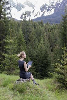 Italy, Alto Adige, Welschnofen, woman sitting in mountainscape using tablet - PSTF00321