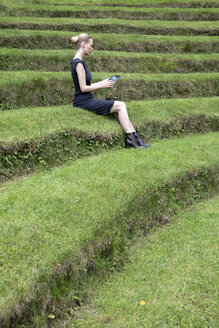 Italy, Alto Adige, Lana, woman sitting on grass-covered steps of natural open air theater using tablet - PSTF00324