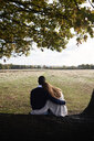 Rear view of couple embracing on tree trunk in a park - IGGF00820