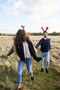 Happy carefree couple wearing Christmassy headdress running in the countryside - IGGF00829