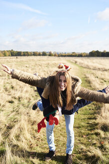 Happy carefree couple wearing Christmassy headdress in the countryside - IGGF00832