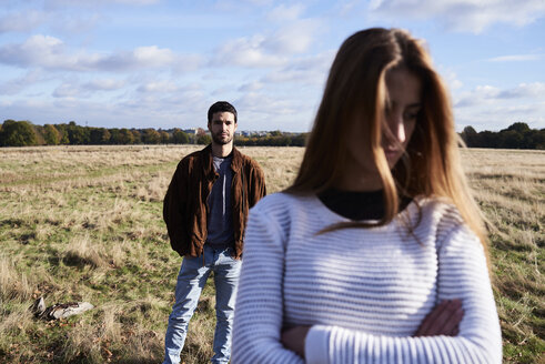 Serious young woman standing on a field with man behind her - IGGF00838
