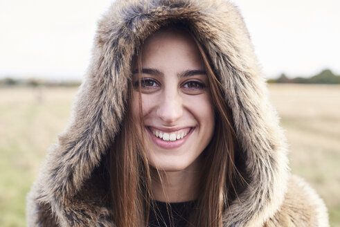 Portrait of beautiful fair-haired girl in fur hood smiling happily at camera in countryside. - IGGF00841