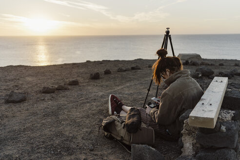 Spain, Canary Islands, Fuerteventura, young woman sitting on the ground using smartphone and digital camera - AFVF02471