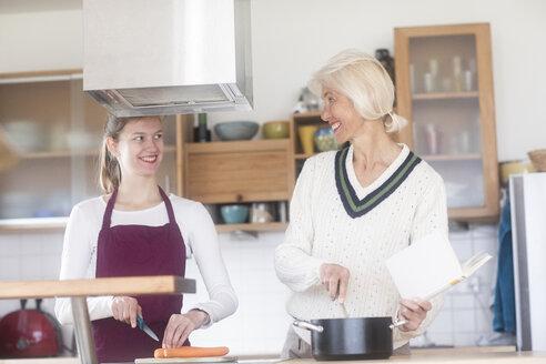 Mutter und Tochter zusammen zu Hause kochend - SGF02311