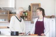 Mother and adult daughter cooking together at home - SGF02314