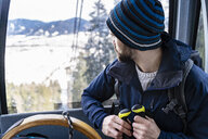Germany, Bavaria, Brauneck, man in winter in gondola lift - DIGF05903