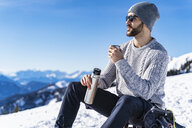 Germany, Bavaria, Brauneck, man in winter in the mountains having a break - DIGF05906